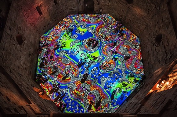 a kaleidoscope of colors  13th century castle courtyard lightened up with psychedelic lights Psychedelic lights modern artists visual art